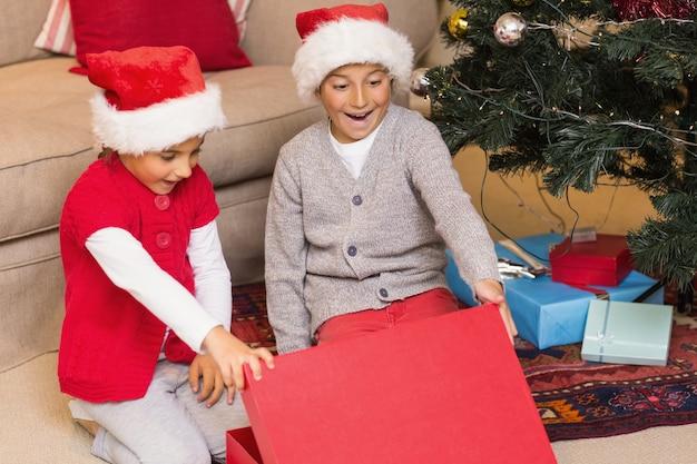 驚いた兄弟姉妹が贈り物を開く
