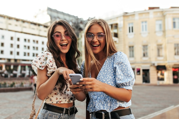 Surprised brunette and blonde women in trendy summer cropped floral blouses and colorful sunglasses smile widely and hold purple phone outdoors