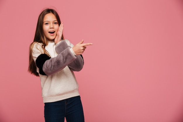 Surprised brunette girl pointing at copy space with opened mouth isolated