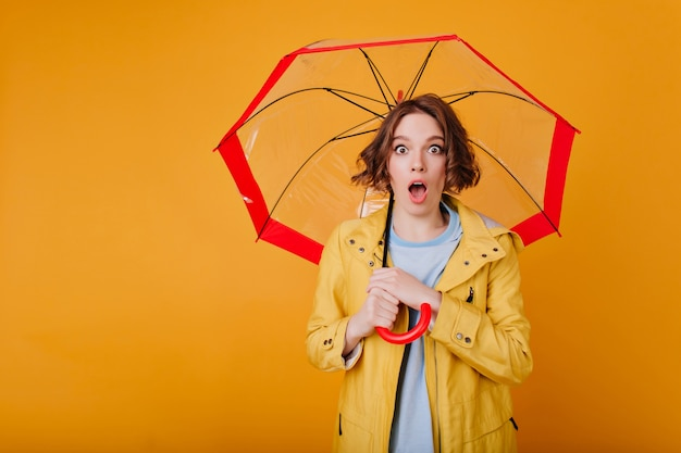 Surprised brunette girl wears trendy bright coat posing with mouth open. indoor photo of shocked lady with wavy hair holding red parasol on yellow wall.