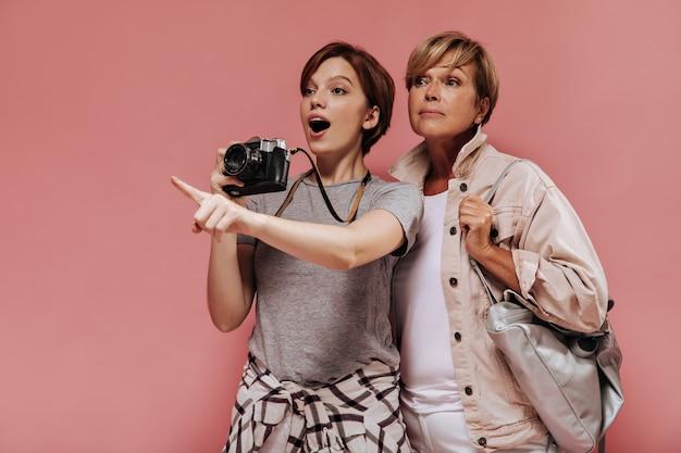 Tシャツを着た驚いたブルネットの女性は指を横に向け、カメラを持って、ピンクの背景に明るい服を着たバッグを持った老婆とポーズをとります。