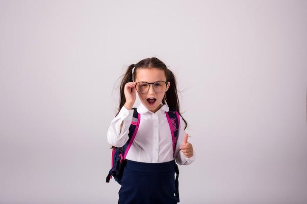 텍스트를 위한 장소와 흰색 배경에 유니폼과 안경에 놀란된 갈색 머리 여학생