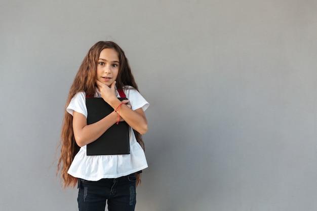 Surprised brunette schoolgirl with long hair hugging book