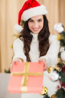 Surprised brunette showing a gift