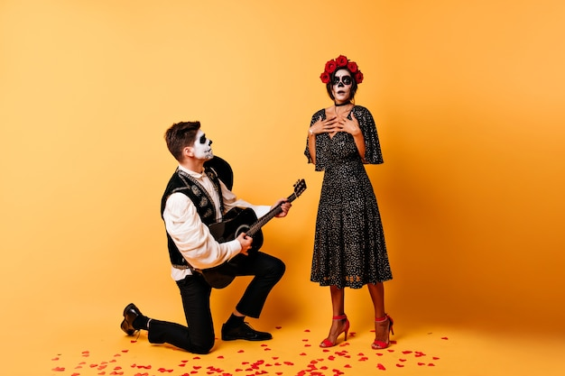 세레나데를 듣고 좀비 카니발 복장에 놀란 된 갈색 머리 여자. 기타를 연주하고 노래하는 가장 무도회 의상에 황홀한 남자의 실내 샷.