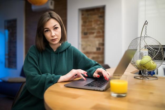 Удивленная брюнетка работает над ноутбуком на кухонном столе и пьет апельсиновый сок