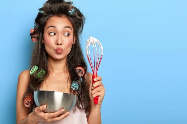 놀란 갈색 머리 여자는 그릇에 사워 크림을 털고, 머리카락 curlers를 착용