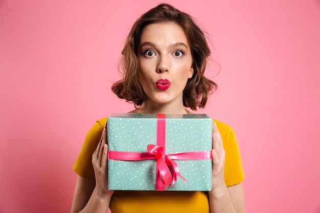 Surprised brunette woman with bright makeup holding present,