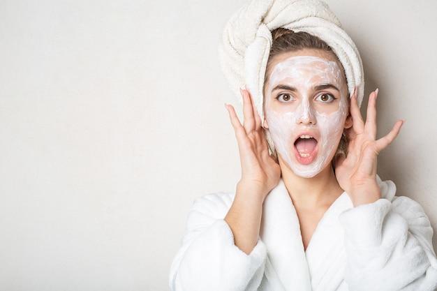 Удивленная брюнетка женщина с увлажняющей крем-маской и банным полотенцем на голове. место для текста