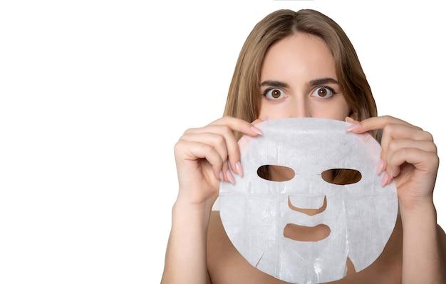 白い背景の上にシートマスクで保湿と驚いたブルネットの女性。テキスト用のスペース