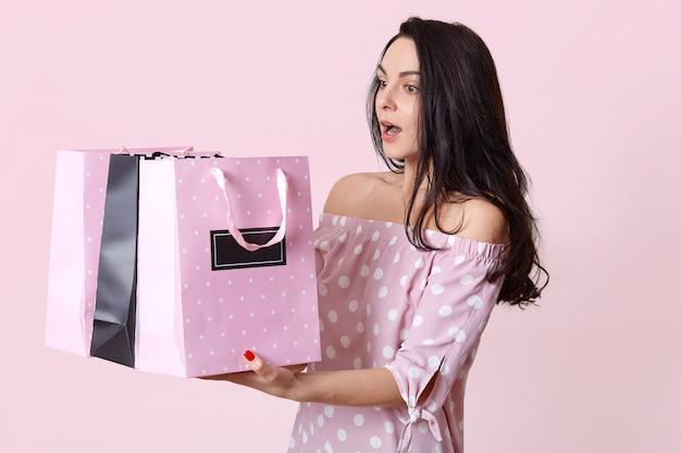 Sorpresa giovane donna bruna ha trattenuto il respiro, trattiene molte borse, ritorna dal negozio con molti acquisti, vestita in abito a pois, isolato su roseo. concetto di shopping