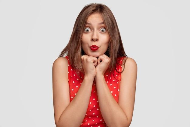 도청 된 눈을 가진 놀란 갈색 머리 젊은 여자, 빨간 입술을 누르고 둥글게 유지, 턱을 잡고, 응시
