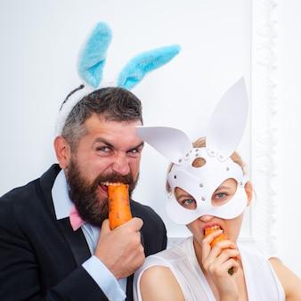 놀란 된 토끼 커플 토끼 귀를 입고 당근을 먹는다. 섹시한 부활절.