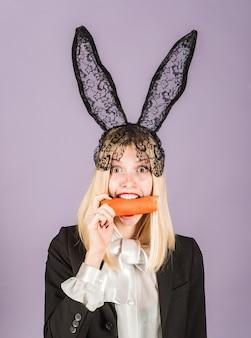 Удивленная женщина кролика носить уши кролика и ест морковь. счастливой пасхи и забавного пасхального дня. улыбнись пасха.