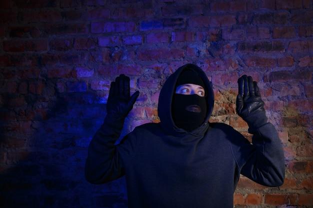 벽돌 벽에 손을 들고 서 있는 놀란 강도