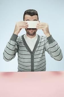 Удивленный деловой человек разговаривает по телефону, сидя за столом