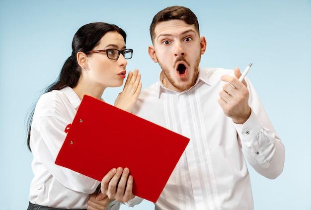 L'uomo d'affari sorpreso e la donna sorridente su uno sfondo blu studio