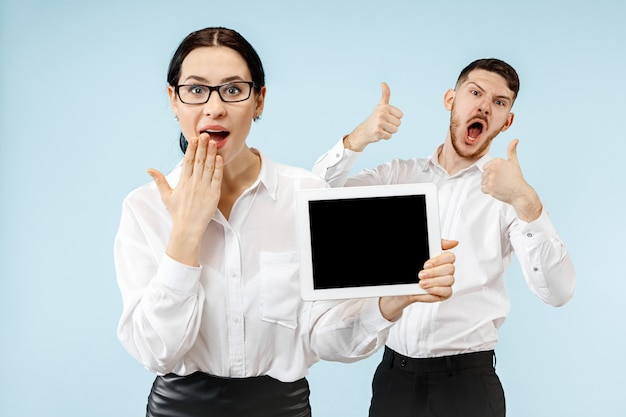 The surprised business man and woman smiling on a blue wall and showing empty screen of laptop or tablet