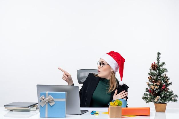 Sorpreso business woman pwith il suo cappello di babbo natale seduto a un tavolo con un albero di natale e un regalo su di esso e concentrato su qualcosa con attenzione su sfondo bianco