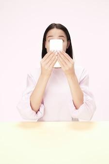 휴대 전화와 유행 핑크 스튜디오 배경에 고립 된 테이블에 앉아 놀된 비즈니스 여자. 아름답고 젊은 얼굴. 여성 절반 길이 초상화.