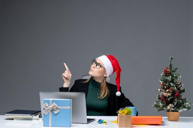 Удивленная деловая женщина в шляпе санта-клауса сидит за столом с рождественским деревом и подарком на нем, указывая выше на темном фоне