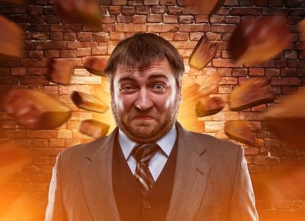 Surprised businessman against blowing brick wall