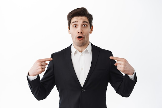 Surprised businessman in black suit gasping, pointing at himself with amazed face, being chosen, standing over white wall