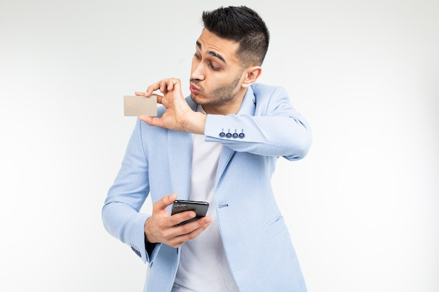 Surprised businessman in a blue jacket with a credit card with a mockup and a smartphone in hand on a white studio background