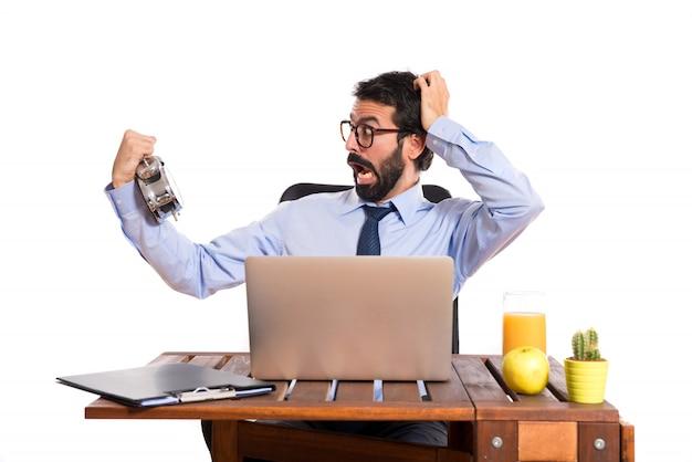 Uomo d'affari sorpreso nel suo ufficio che tiene un orologio