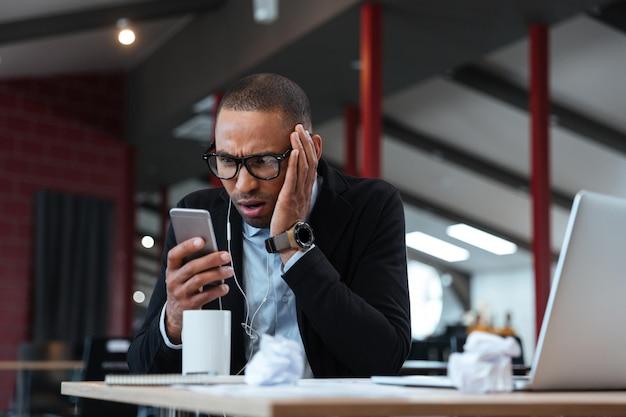 Удивленный бизнесмен смотрит на смартфон и носит наушники