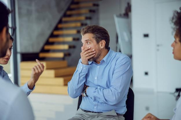 Удивленный бизнесмен сидит в кругу с группой поддержки и был шокирован