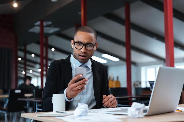 Удивленный бизнесмен текстовых сообщений на смартфоне в офисе