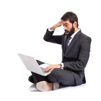 Uomo d'affari sorpreso con computer portatile su sfondo bianco