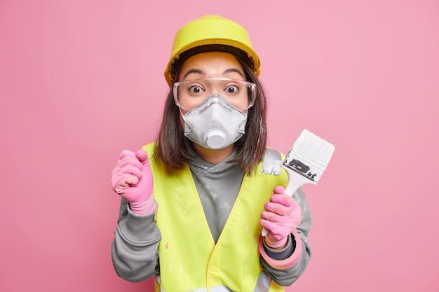 놀란 바쁜 아시아 여성 장식가는 뉴스에 들떠 주먹을 꽉 쥐고 벽에 페인트를 칠하고 페인트 브러시를 착용하고 보호용 호흡기를 착용합니다