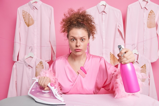 Surprised busy curly haired european housewife holds detergent spray and electric iron uses electric appliance dressed in domestic gown isolated over pink wall with hanging ironed shirts