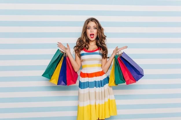 Удивленная большими скидками в любимом магазине девушка позирует на светлой полосатой стене в ярком летнем платье. крытый женский портрет с красочными сумками