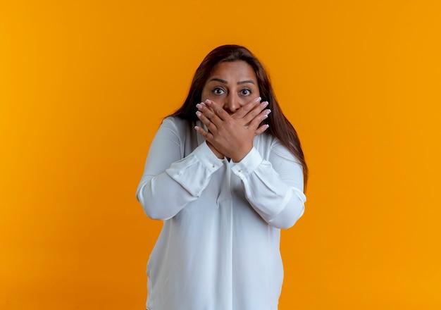 놀란 캐주얼 백인 중년 여성이 노란색 벽에 고립 된 손으로 입을 덮었습니다.
