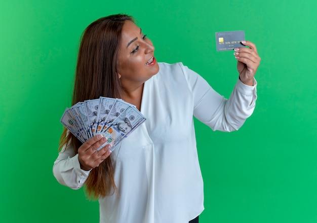 Удивленная случайная кавказская женщина средних лет, держащая наличные и смотрящая на кредитную карту в руке на зеленом фоне