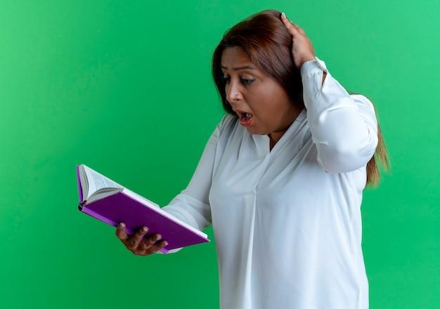 Donna di mezza età caucasica casuale sorpresa che tiene e che esamina il libro e che mette la mano sulla testa isolata sulla parete verde