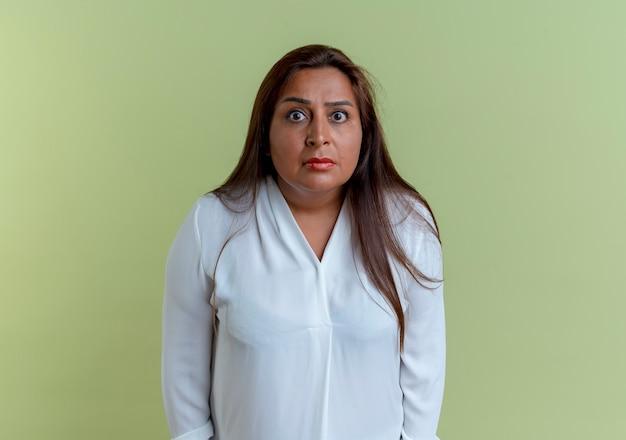 Удивленная случайная кавказская женщина средних лет изолирована на оливково-зеленой стене
