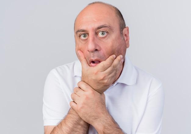 Uomo d'affari maturo casuale sorpreso che guarda l'obbiettivo che tiene il mento e il polso isolati su fondo bianco