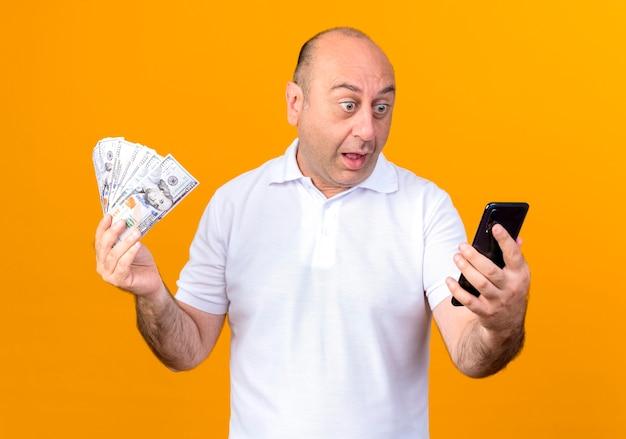 Uomo maturo casuale sorpreso che tiene contanti e che esamina telefono isolato sulla parete gialla