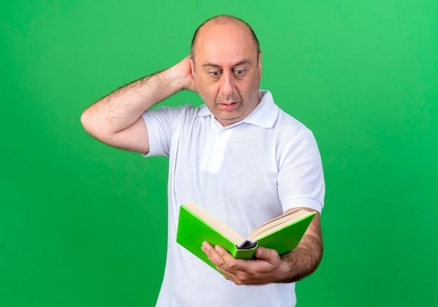 Uomo maturo casuale sorpreso che tiene e che esamina il libro e che mette la mano dietro la testa isolata sulla parete verde