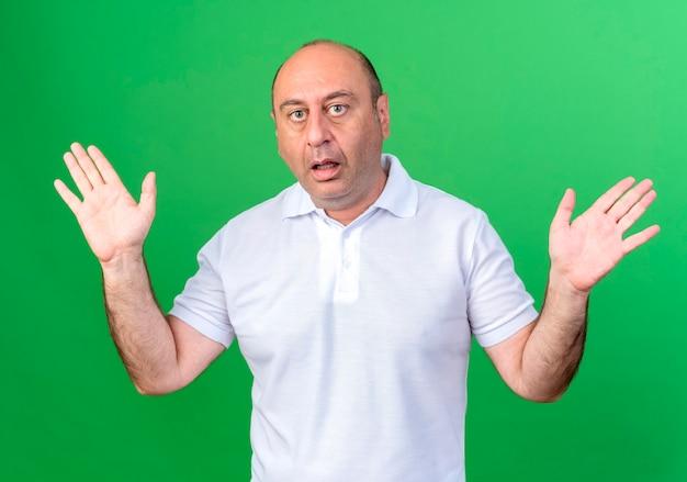 驚いたカジュアルな成熟した男は、緑の壁に隔離された手を広げます