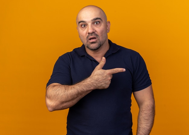Surprised casual middle-aged man looking at front pointing at side isolated on orange wall