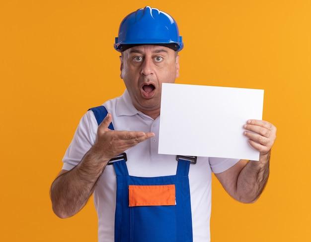 オレンジ色の白紙のシートを保持し、ポイントする制服を着た驚いた白人の大人のビルダーの男