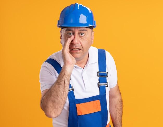 L'uomo adulto caucasico sorpreso del costruttore in uniforme tiene la mano vicino alla bocca sull'arancio