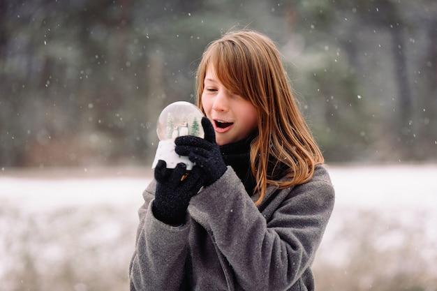Surprised caucasian blonde girl examines a magic glass snow globe. winter season scene. falling