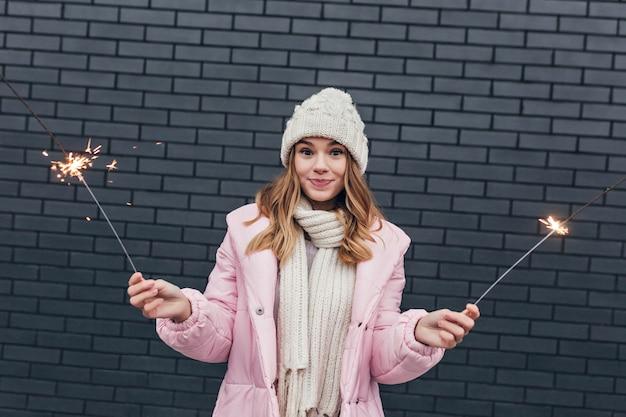 Ragazza caucasica sorpresa in cappotto rosa che posa con le luci del bengala. foto all'aperto di blithesome signora bionda che tiene le stelle filanti.