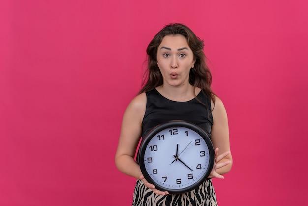 ピンクの背景に壁時計を保持している黒のアンダーシャツを着て驚いた白人少女